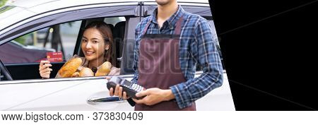 Asian woman make mobile payment contactless technology for online grocery ordering and drive thru service. Drive through is popular after pandemic. Panorama web banner with free copyspace for editing.
