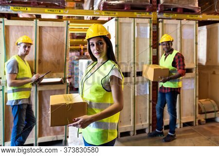Portrait of caucasian white woman warehouse worker hold parcel box with her colleague working about stock in warehouse distribution center environment. Using in business warehouse and logistic concept