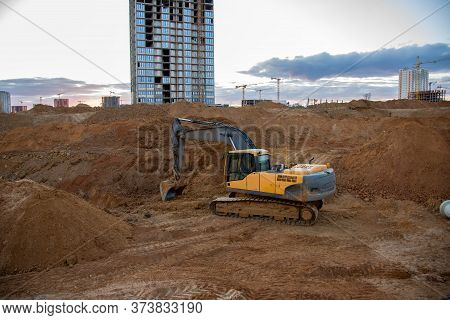 Excavator Working At Construction Site On Earthworks. Backhoe Digs Ground For Laying Concrete Pipes.