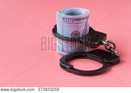 Twisted Wad Of Dollars Buttoned With Handcuffs On A Pink Background