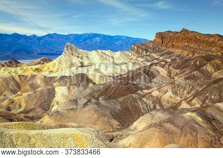 Magnificent erosion landscape of various shades. Death Valley in California, USA. Sunset. Zabriskie Point is part of the Amargosa Range. The concept of active, extreme and photo tourism