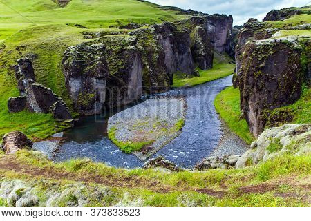 The most beautiful and mysterious canyon in Iceland - Fyadrarglyufur Canyon. Sheer cliffs stand along a stream with melted glacial water. The concept of active, eco and photo tourism