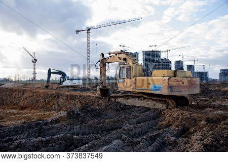 Excavators Working At Construction Site On Earthworks. Backhoe Digging Building Foundation. Paving O