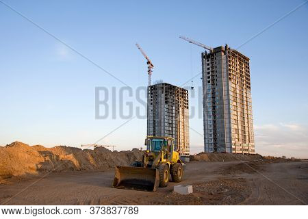 Front-end Loader Working At Construction Site. Earth-moving Heavy Equipment For Road Work. Tower Cra