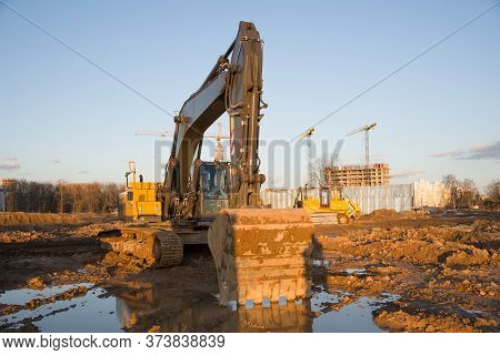 Excavator And Dozer Working At Construction Site On Earthworks. Backhoe On Road Work Digs Ground. Pa