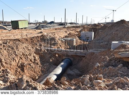 Installation Of Concrete Sewer Wells And Pipe Drainage In The Ground. Laying Heating Pipes In A Tren