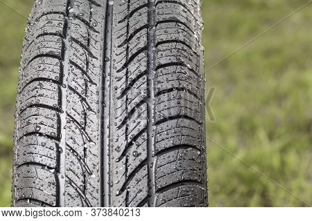 New Tire. There Are Raindrops On It. The Tread Pattern Is Looking At Us. Close-up.