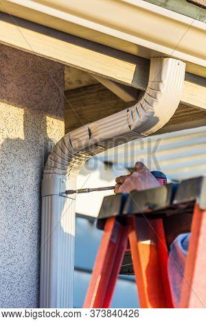 Worker Attaching Aluminum Rain Gutter and Down Spou