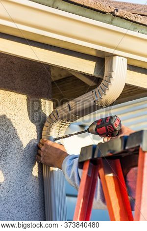 Worker Attaching Aluminum Rain Gutter and Down Spout