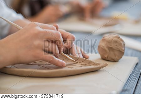 Female Potters Hand Making Clay Pottery At The Table With A Different Wooden Tools Close Up.