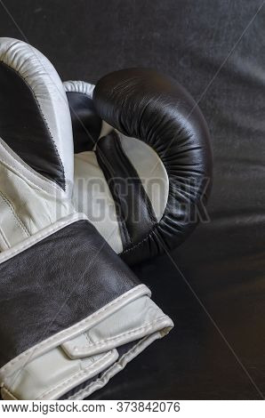 Pair Of Leather Boxing Gloves On The Black Floor Of A Boxing Ring. Black And White Gloves For Boxing