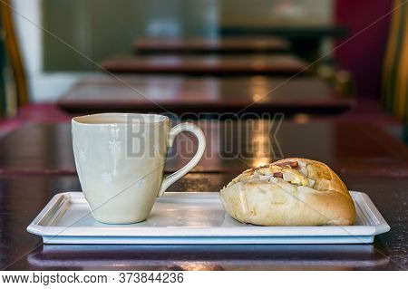 A Coffee Latte Mug And A Sweet Bread With Jam And Cheese On A Tray Over A Coffee Shop Background.