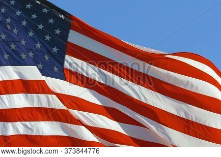 Closeup Of Large American Flag Waving In Front Of Blue Sky. Us Flag - American Flag Waving In Wind.