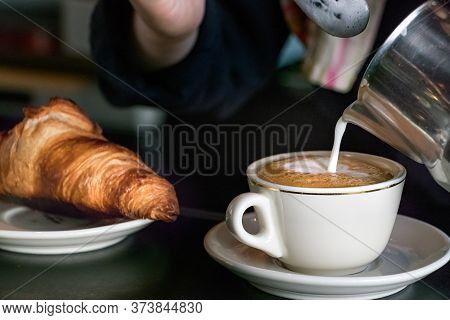Barista Female Hands Pouring Hot Milk On A Cup To Make A Cappuccino Beside A Croissant.