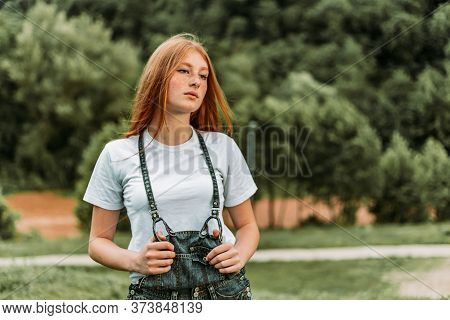 Portrait Of Young Teen Freckled Ginger Girl Holding Onto Her Suspender In A Cocky Way