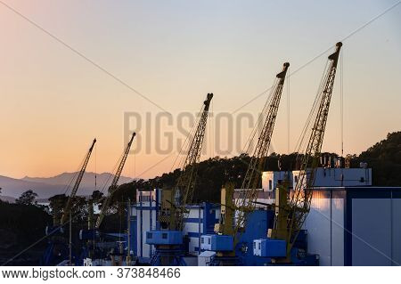 Shipping Cranes In The Port Of Petropavlovsk, Russia At Sunset.