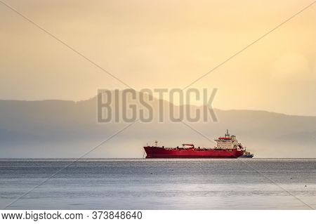 A Red Tanker Ship Sailing At High Seas In The Bering Sea At Sunset.