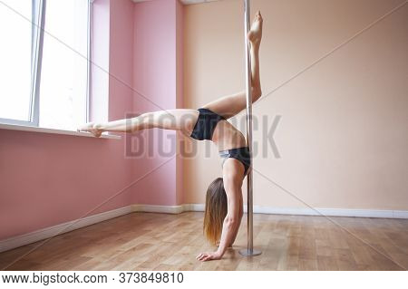 Pole Dance Training, Athletic Girl Does Exercise On A Pylon, Gymnast Does A Difficult Trick