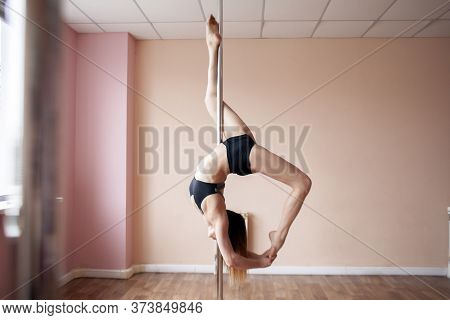 Sports Girl Is Practicing Pole Dance And Doing The Trick, The Gymnast Is Hanging On The Pylon And Do