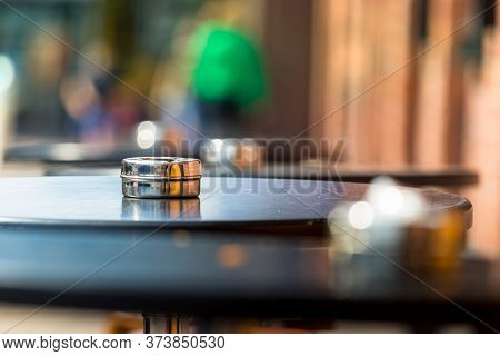 An Ashtray Placed On A Round Wooden Table Outdors, Shallow Dof.