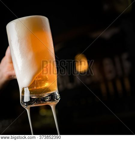 Hand With Beer Mug, Toasting In Celebration, With Overflowing Foam, Dark Background And Space For Wr