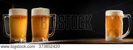 Three Cold Mugs With Beer, With Overflowing Foam, On Wooden Table And Dark Background, Space For Wri