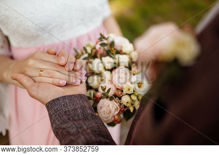 Hands Of Newlyweds With Wedding Rings And A Wedding Bouquetf. Newlyweds With Wedding Rings And A Wed