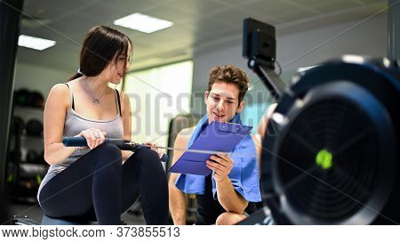 Young woman working out on the rowing machine, personal trainer explaining the technique to her