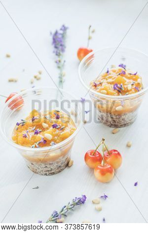Two Cups Of Granola Breakfast Served With Lavender Flowers, Fruit Jam And Cherry On A Wooden Tray. C