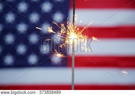 4th of July. A Golden Sparkler burns with an American Flag background. American Pride.