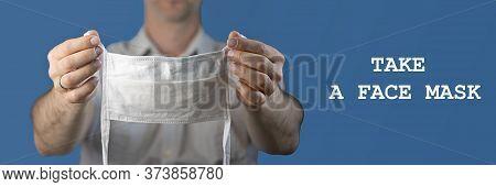 Preventive White Medical Mask In Defocused Unrecognizable Mans Hands. Indoor Studio Shot On Blue Bac