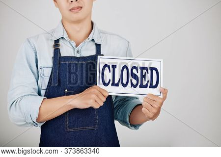 Cropped Image Of Sad Young Coffeeshop Owner Showing Closed Sign
