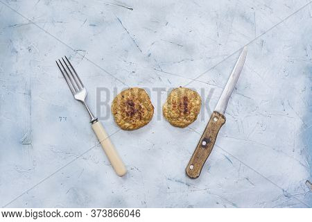 Oats Cutlets And Banana Slices With A Knife And Fork On The Table. Healthy Diet Eating. Special Food