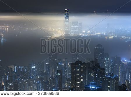 Foggy Night View Of Victoria Harbor In Hong Kong City