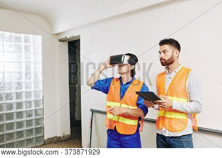 Contractor And Builder Using Application For Virtual Reality Headset To Check Wiring And Pipes In Ho