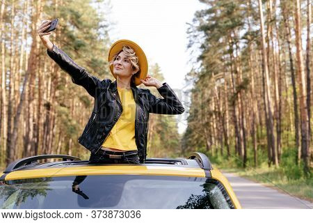 Girl Standing Out Of Car Sunroof Summer Road Trip. Girl In Leather Jacket, Hat And Sunglasses At Joy