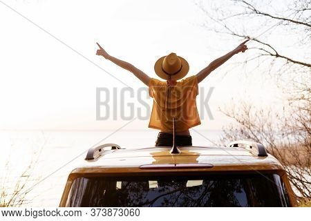 Woman Spread Arms Widely At Car Sunroof Back View. Young Girl With Outstretched Hands Weekend Getawa