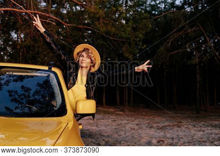 Caucasian Smiling Woman Leaning Out Of Car Window. Female Driver Have Fun During Auto Journey Front