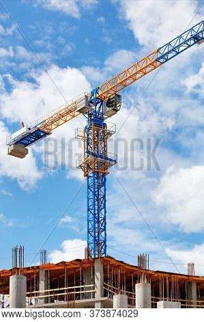 The Arrow Of A Yellow And Blue High-rise Tower Crane Rises Above The Construction Site Diagonally Ag