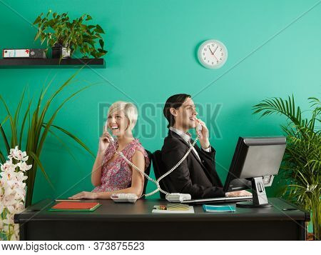 Two business people talking on entangled phones in office