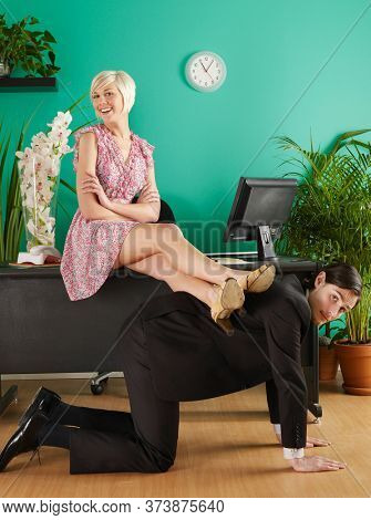 Female office worker resting legs on man kneeling on hands and knees in office portrait