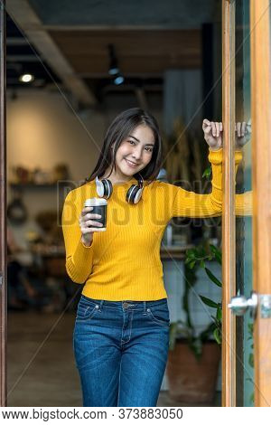 Asian Young Female Holding A Cup Of Coffee In Modern Coffee Shop Or Coworking Space Beside Coffee Es