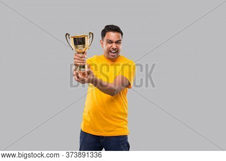 Indian Man Very Happy And Excited, Raising Arms, Celebrating A Victory Or Success Holding Trophy. Wi