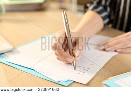 Close Up Of Woman Hands Filling Out Application Form Sitting On A Desk At Home
