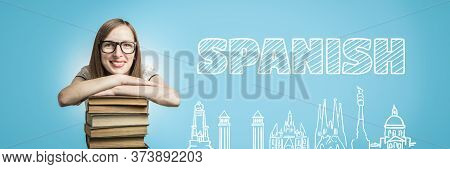 Young Girl In A White Dress And Glasses Put Her Hands On A Stack Of Books On A Blue Background. Adde