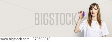 Happy Young Woman Holds An Inhaler In Her Hand, Looks At The Inhaler On A Light Background. Banner.