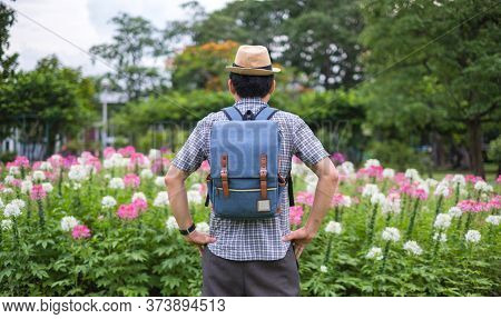 Young Man Tourists Backpack Are Sitting Visit Spider Flower Garden. During Traveling In The Holidays