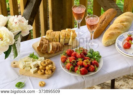 Summer Picnic Table With Various Snacks And Rose Wine Outdoors