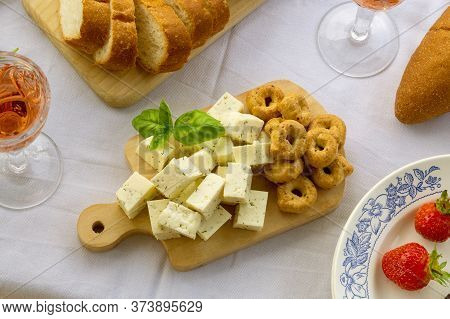 Rose Wine And Various Appetizers On A White Textile Background