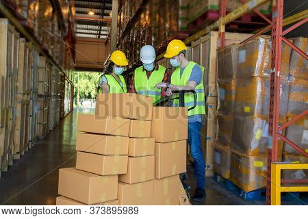 Warehouse Workers Wearing Protective Mask To Protect Against Covid-19 With Clipboard During Work In